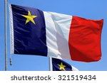 Small photo of Acadian Flag with Blue Sky Background, Newfoundland, Canada
