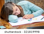 Small photo of Tired or despondent young girl do homework lying on a table