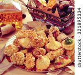 Small photo of closeup of a plate with panellets, some roasted chestnuts and sweet potatoes in a basket, and sweet wine in a glass bottle, typical snack in All Saints Day in Catalonia, Spain