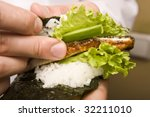 Cook on kitchen prepares Japanese susi - stock photo