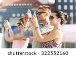 friendship, leisure, summer, technology and people concept - group of smiling friends with smartphone taking picture outdoors - stock photo