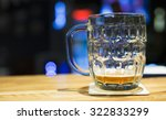 Small photo of Almost empty glass mug of tasty craft beer in pub
