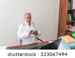 Small photo of Aback doctor in his studio, uses a tablet in front of his laptop. Use new technologies. In his professional studio, he is sitting at antique desk, and a green lamp shade of green.