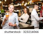 smiling girl standing at bar... | Shutterstock . vector #323216066