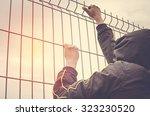 refugee men and metal fence....   Shutterstock . vector #323230520