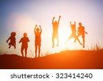 silhouette of children jump... | Shutterstock . vector #323414240