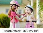 little girl helping her sister... | Shutterstock . vector #323499104