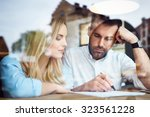 couple at cafe reading bank... | Shutterstock . vector #323561228