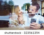 couple at cafe laughing while... | Shutterstock . vector #323561354