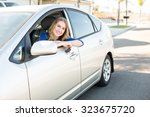 young woman sitting in her car... | Shutterstock . vector #323675720