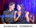 young flirty couple with wine... | Shutterstock . vector #323680610