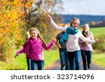 family take walk in autumn... | Shutterstock . vector #323714096