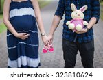 future parents holding hands... | Shutterstock . vector #323810624