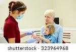 pediatric dentist explaining to ... | Shutterstock . vector #323964968