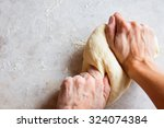 Hands Kneading Dough On White...