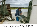 Commercial Fisherman Mends His...