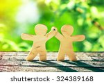 wooden little men holding hands ... | Shutterstock . vector #324389168