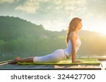 Woman Doing Yoga On The Lake  ...
