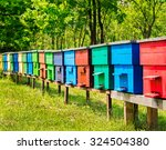 Row Of Colorful Wooden Beehive...