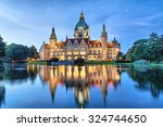 Stock photo new city hall of hannover reflecting in water in the evening lower saxony germany 324744650