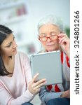 helping old woman use a tablet... | Shutterstock . vector #324801266