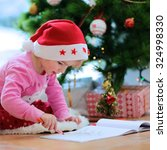 Small photo of Cute little kid writes letter to Santa. Adorable toddler girl in Santa hat lying on the floor on lambskin carpet next to big window. Christmas tree with lights and gifts at the background.