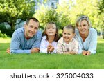 family lying on the grass and...   Shutterstock . vector #325004033