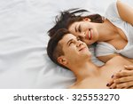 lovely young couple lying on... | Shutterstock . vector #325553270