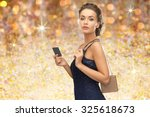Small photo of people, luxury, holidays and finance concept - beautiful woman in evening dress with vip card and handbag over golden lights background