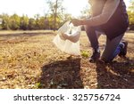 young man picking up trash... | Shutterstock . vector #325756724