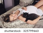 Stock photo cute smiling pregnant woman lying in bed with black cat 325799663