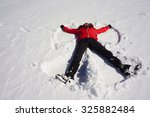 Girl Making A Snow Angel In Th...