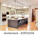 Stock photo kitchen interior with island sink cabinets and hardwood floors in new luxury home 325910156