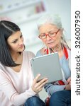 helping old woman use a tablet... | Shutterstock . vector #326007950
