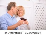 Small photo of Pleasant affinity. Cheerful delighted adult couple holding glasses and drinking wine while bonding to each other