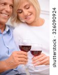 Small photo of Sweet moment. Vivacious agreeable adult couple bonding to each other and expressing love while drinking wine