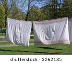 washed drying bedclothes hanged out in yard - stock photo