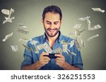 Small photo of Technology online banking money transfer, e-commerce concept. Happy young man using smartphone with dollar bills flying away from screen isolated on gray wall office background.