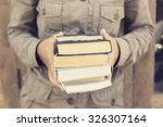 girl carrying a pack of books | Shutterstock . vector #326307164