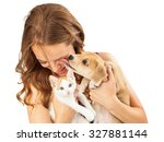 Stock photo a pretty young girl holding a cute orange tabby kitten and an affectionate puppy that is licking 327881144