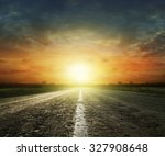 Stock photo long country road with white lines down the centre stretching off past a lone tree to the distant 327908648