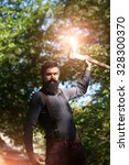 Small photo of One handsome strong stylish male logger of young man with long lush black beard and moustache in shirt holding wooden axe standing near tree outdoor on natural background, vertical