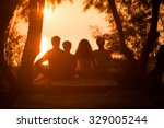 Silhouette Of A Family Sitting...