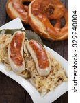 Small photo of German white sausage or wurst served with sauerkraut and pretzel