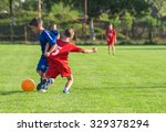 boys kicking football on the... | Shutterstock . vector #329378294