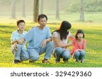 family lying outdoors being... | Shutterstock . vector #329429360
