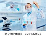 young chemist analyzing liquids ... | Shutterstock . vector #329432573
