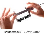 """Small photo of Color horizontal shot of two hands holding a caliper and measuring the word """"ignorance""""."""