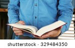 male hands holding open book on ...   Shutterstock . vector #329484350