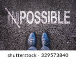 Small photo of Changing the word impossible on possible on an asphalt road with feet